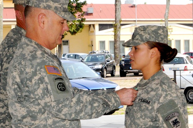 Sgt. Irene Lopez, USARAF G1 (Personnel), receives an Army Commendation medal USARAF Commander Maj. Gen. Patrick Donahue during the quarterly battalion awards ceremony at Hoekstra Field Aug. 23.