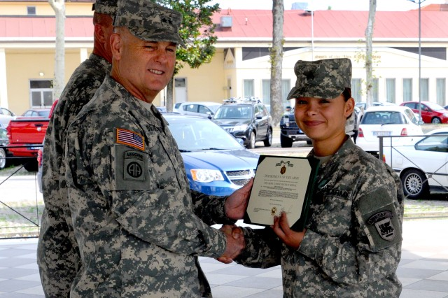 Sgt. Irene Lopez, USARAF G1 (Personnel), receives an Army Commendation medal from the USARAF Commander, Maj. Gen. Patrick Donahue during the quarterly battalion awards ceremony at Hoekstra Field Aug. 23.