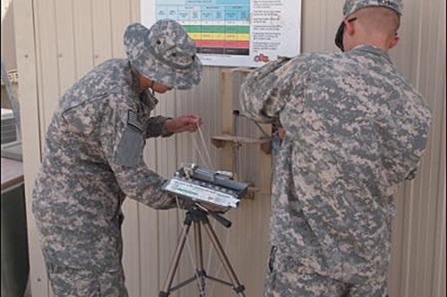 Fourth Battalion, 3rd Air Defense Artillery Soldiers do an hourly wet bulb check outside the battalion aid station at their deployed location in Kuwait.