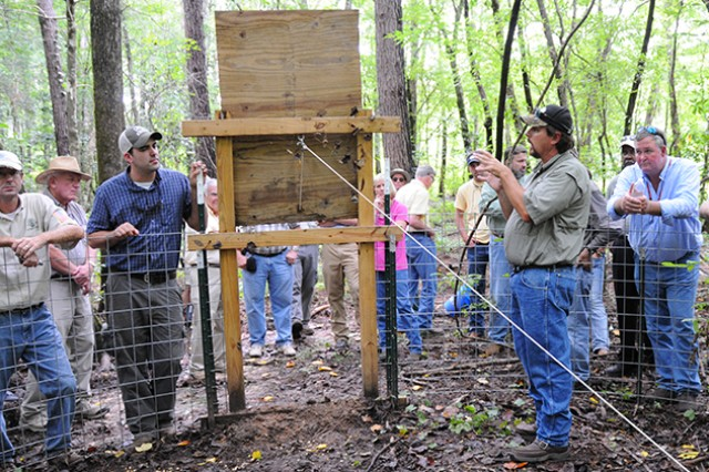 James Bruner, wildlife biologist, explains the construction and workings of one of the pig traps located on Fort Rucker during the Wildlife School for Landowners day in the field Aug. 23.