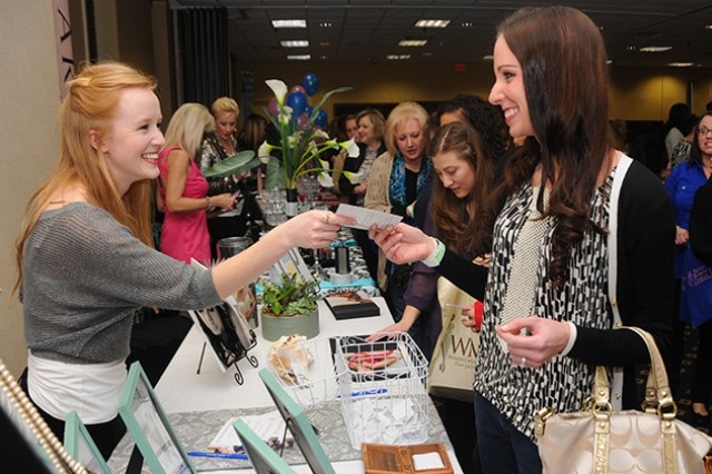Lisa Sargent, Army spouse, takes a brochure from Michelle Balducci-Connelly, Michelle Marie Photography, at the last Girls Night Out event held in March at The Landing.