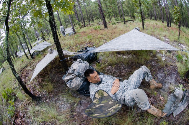 An infantryman with the 82nd Airborne Division's 1st Brigade Combat Team rests outside his hooch, or outdoor dwelling, before heading out with his squad to attack a notional enemy position, Aug. 20, at Fort Bragg, N.C. The paratroopers slung ponchos to trees to sleep under in preparation for a predicted evening downpour. (U.S. Army photo by Staff Sgt. Mary S. Katzenberger)