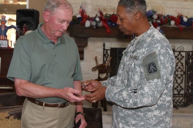 "FORT SAM HOUSTON, Texas - Maj. Gen. Adolph McQueen Jr., deputy commanding general for support, U.S. Army North (Fifth Army), presents an Army North lapel pin to Gary Baber Aug. 20 to express his appreciation for the volunteer work Baber's organization provides for the Warrior and Family Support Center. Barber's organization, the Red River Valley Fighter Pilots Association, has helped the WFSC provide assistance to wounded warriors and their families for the last eight years through donations and volunteer support.  McQueen presented certificates, personal notes of appreciation and Army North lapel pins to Barber and nine fellow WFSC volunteers for their dedication during two separate ceremonies Aug. 20 and 22. ""I cannot thank you enough for the service you provide to our wounded warriors,"" said McQueen. (U.S. Army photo by Staff Sgt. Corey Baltos, Army North PAO)"