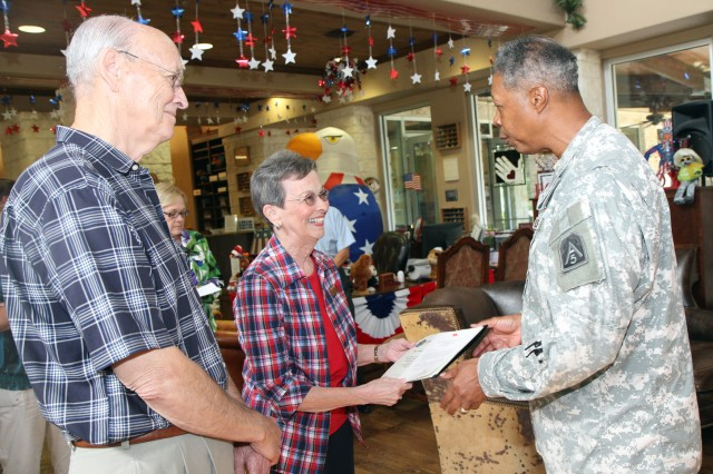 "FORT SAM HOUSTON, Texas - John and Betty Thompson smile and share a quiet moment together as Maj. Gen. Adolph McQueen Jr., deputy commanding general for support, U.S. Army North (Fifth Army), expresses his thanks Aug. 22 for their volunteer efforts at the Warrior and Family Support Center over the years. The Thompsons are known throughout the WFSC as ""the cookie people"" because they make homemade cookies for the wounded warriors every week. ""You make this place smell like a million dollars,"" said McQueen, as he presents them an Army North certificate of appreciation as well as a personal letter of appreciation from him. McQueen thanked 10 volunteers during two separate ceremonies Aug. 20 and 22. (U.S. Army photo by Staff Sgt. Corey Baltos, Army North PAO)"