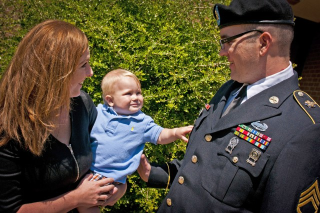 Staff Sgt. Patrick Zeigler, his wife Jessica, and their son, Liam, enjoy a moment in the sun outside Fort Hood's Survivor Outreach Services building while waiting for the verdict in the court-martial of Maj. Nidal Hasan, who was accused of carrying out the Nov. 5, 2009 shooting rampage that killed 13 and wounded 32 on, Aug. 26, 2013. Zeigler, who was in the building that the shooting took place getting cleared to attend Officer Candidate School, was shot four times in the incident, including once in the head that necessitated the removal of 20 percent of his brain. Hasan was found guilty of the shootings less than an hour after this photo was taken, and sentenced to death two days later. (U.S. Army photo by Sgt. Ken Scar, 7th Mobile Public Affairs Detachment)