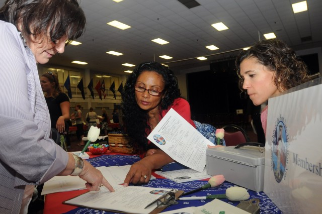 "FORT SAM HOUSTON, Texas "" Barbara Becerra (left) gets a helping hand in filling out membership forms from Chelle Evans (center) and Tina Krompecher during the Fort Sam Spouses' Club membership drive and luncheon Aug. 27 at the Army Community Services building. Evans represents Installation Management Command and Krompecher represents U.S. Army North (Fifth Army). (U.S. Army photo by Sgt. 1st Class Christopher DeHart, Army North PAO)"