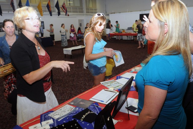 FORT SAM HOUSTON, Texas - Joy Kellner (left), president of the Fort Sam Spouses' Club, speaks with Magyn Whitaker, a vendor, during the Spouses' Club membership drive and luncheon Aug. 27 at the Army Community Services building. (U.S. Army photo by Sgt. 1st Class Christopher DeHart, Army North PAO)