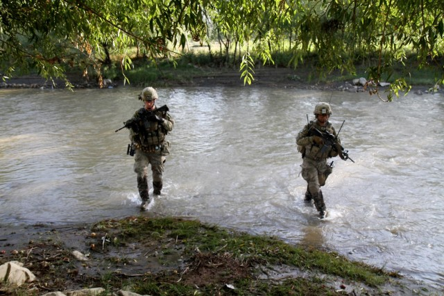 U.S. Army 2nd Lt. William Clapp, left, infantry platoon leader, and U.S. Army Spc. Ronnie Ancheta, a radio operator, both with Company A, 3rd Battalion, 15th Infantry Regiment, 4th Infantry Brigade Combat Team, 3rd Infantry Division, cross a small stream in Wardak province, Afghanistan, Aug. 21, 2013, while on a foot patrol in order to secure the area. (U.S. Army photo by Sgt. Bob Yarbrough, 4th IBCT, 3rd Inf. Div., Public Affairs)