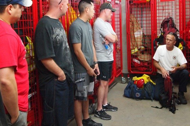 From left, Soldiers from the 12th Platoon, Advanced Leadership Course, Noncommissioned Officers Academy, learn about wildland firefighting equipment from Dave Rhodes,, captain, Fort Huachuca Fire Department, Station 2. Before Soldiers washed station vehicles, they received a tour and briefing about selected fire gear on Saturday.