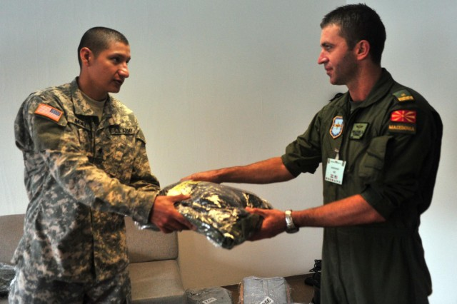 U.S. Army Spc. Fausto F. Jimenez, left, a human resources specialist assigned to the 16th Sustainment Brigade headquarters and a native of Tyler, Texas, hands Macedonian Maj. Dragam Pavlovski, a member of the Macedonian Air Force Brigade and a native of Kumanovo, Macedonia, his laundry during Operation Immediate Response 13 at Petar Zrinski Barracks Aug. 28. Jimenez was a member of the IR13 Mayor's Cell which was responsible for providing billeting, laundry service and food for training participants.
