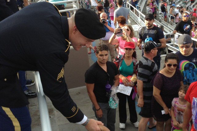 Staff Sgt. Ty M. Carter greets kids and poses for pics with families after being honored at sea world San Diego for his service.  Carter received the Medal of Honor during a ceremony at the White House, Aug. 26, 2013, for extraordinary gallantry and selfless actions during the Battle of Kamdesh at Combat Outpost Keating, Afghanistan, on Oct. 3, 2009. Carter was also inducted into the Pentagon's Hall of Heroes, Aug. 27.