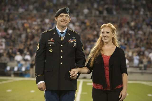 Staff Sgt. Ty Michael Carter and his wife Shannon receive a standing ovation from the Michie Stadium crowd at the U.S. Military Academy at West Point, N.Y., during the Army vs. Morgan State game, Aug. 30, 2013. Carter received the Medal of Honor during a ceremony at the White House, Aug. 26, 2013, for extraordinary gallantry and selfless actions during the Battle of Kamdesh at Combat Outpost Keating, Afghanistan, on Oct. 3, 2009. Carter was also inducted into the Pentagon's Hall of Heroes, Aug. 27.