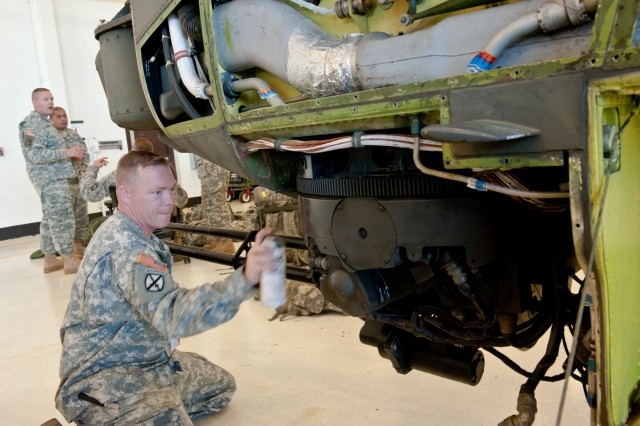 Sgt. Steven Gould, with B Company, 96th Aviation Support Battalion, 101st Airborne Division (Air Assault), paints the mount of the 20mm gun during the restoration of an AH-1F Cobra Helicopter at Fort Campbell, Ky., Aug. 8, 2013.