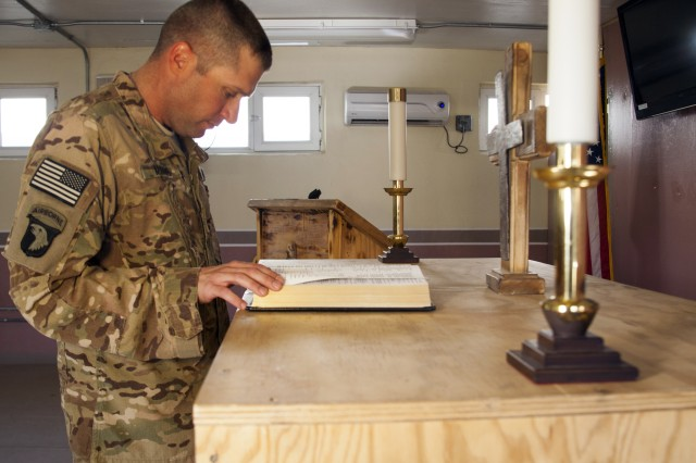 """CAMP SABALU-HARRISON, Afghanistan """" Task Force Vigilant Ministry Noncommissioned Officer in Charge Staff Sgt. Robert Mathis reads his favorite Psalm in the Camp Sabalu-Harrison Chapel, Aug. 15, 2013. Mathis, once an infantryman, now serves as a chaplain's assistant after suffering injuries in an enemy attack in Iraq in April 2003."""