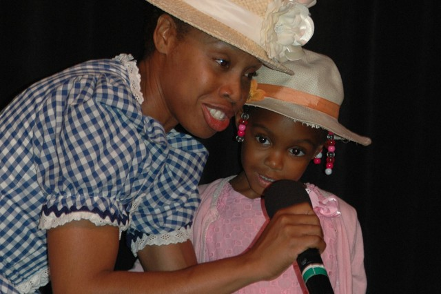 Sgt. Radia Marquis, 106th Finance Company, sings the Sister Suffragette song with her daughter, Rachel, during the Women's Equality Day celebration Aug. 26 in Vicenza, Italy. Additional, a ceremonial walk with mock protest signs for women's rights was done.