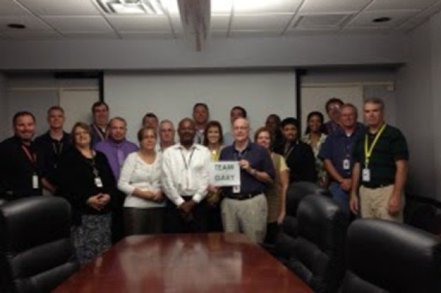 "Corps employee Gary East shares a ""Team Gary"" sign with co-workers at Huntsville Center in August."