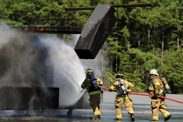 U.S. Army Garrison Fort A.P. Hill firefighters honed their skills today during aircraft fire training on post. The mock aircraft is fitted with propane-fired burners which simulate a fire of different sizes. When they roll onto the scene firefighters first hit the blaze with the water cannons atop their truck. Then, they dismount and use a steady stream of water from a fire hose to quell the flames. As fire dies, the firefighters apply a water fog to finish the job.