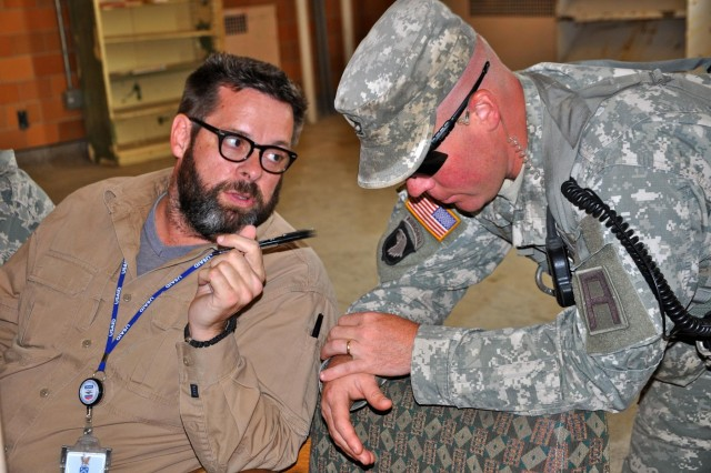 Edward Vowell, state department, speaks with Sgt. 1st Class Benjamin Roos, a trainer/mentor with the 1-335th Infantry Battalion, 205th Infantry Bridge, during a key leader engagement training opportunity. The Foreign Service Institute, the training arm of the State Department, mandates all government civilians attend training before they deploy. Recently, First Army Division East incorporated Indiana National Guard Soldiers providing operational security into the scenario.