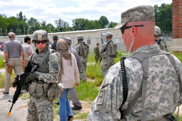 Sgt. 1st Class Benjamin Roos, a trainer/mentor with the 1-335th Infantry Battalion, 205th Infantry Bridge, observes while Indiana National Guard Soldiers provide security for personnel from the Department of State, Department of Agriculture and the U.S. Agency for International Development before a Key Leadership Engagement during the Foreign Service Institute training at Muscatatuck Urban Training Center, Ind.