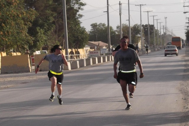 Staff Sgt. Maria Morales and Pfc. Moody Watson, both assigned to Headquarters and Headquarters Company, 555th Engineer Brigade, sprint to the finish during a recent eight-mile run around Bagram Airfield, Afghanistan, Aug. 17, 2013. The 555th Eng. Bde., Joint Task Force Triple Nickel, from Joint Base Lewis-McChord, Wash., is nearing the end of its deployment to Afghanistan as the U.S. Theater Engineer Brigade in support of the International Security Assistance Force.