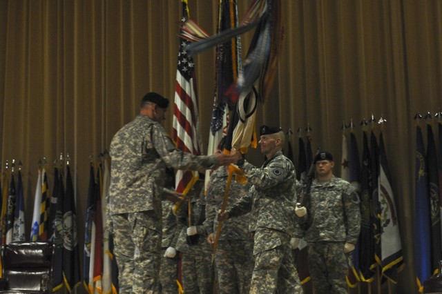 Command Sgt. Maj. John W. Troxell, outgoing I Corps command sergeant major, hands I Corps commander Lt. Gen. Robert Brown the corps colors as he relinquishes the responsibilities to incoming I Corps command sergeant major, Command Sgt. Maj. James Norman, in a ceremony Sept. 3. (U.S. Army photo by Spc. Leon Cook)