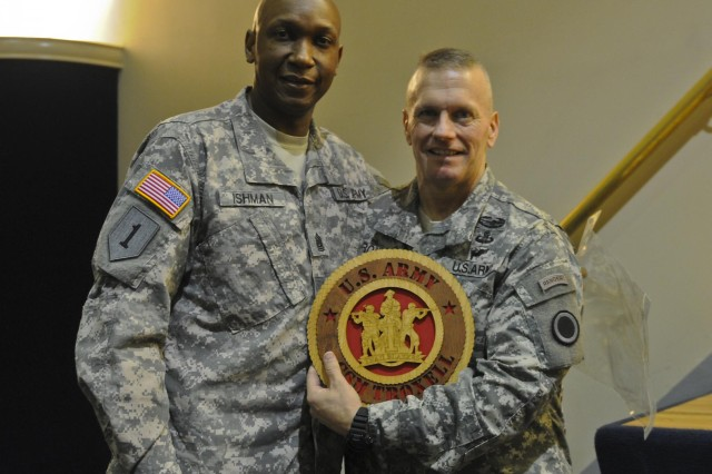 Command Sgt. Maj. Woodrow Ishman, command sergeant major for Headquarters and Headquarters Battalion, I Corps, presents former I Corps Command Sgt. Maj. John W. Troxell with a plaque commemorating his time with the corps after Troxell's change of responsibility ceremony Sept. 3. Troxell relinquished his responsibilities as corps command sergeant to Command Sgt. Maj. James Norman. (U.S. Army photo by Spc. Leon Cook)