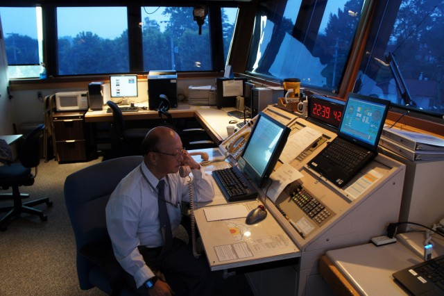 Air traffic control specialist Chang Pong-gyu, who served Yongsan for the past 52 years, answers a call during his work hours in the Yongsan heliport control tower. (Courtesy photo)
