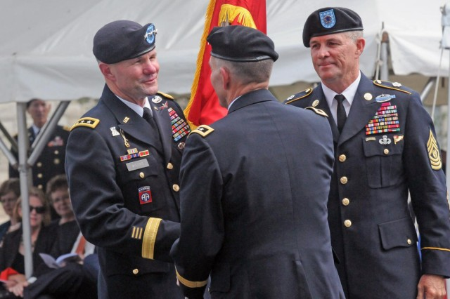 Lt. Gen. Perry Wiggins receives the U.S. Army North (Fifth Army) colors from Lt. Gen. William Caldwell IV as he assumes command while Command Sgt. Maj. Hu Rhodes looks, Sept. 4, 2013, during a change-of-command ceremony held in the historic Quadrangle on Fort Sam Houston, Texas. Wiggins, who previously served as the deputy commanding general for Army North and was promoted prior to the ceremony to the rank of lieutenant general, then assumed duties as commanding general, Army North, and senior commander for Fort Sam Houston and Camp Bullis. Caldwell departs command of Fifth Army, the same command his father, retired Lt. Gen. William Caldwell III, held before he retired in 1980, both in their 37th year of service. Rhodes is the senior enlisted adviser for Army North, Fort Sam Houston and Camp Bullis.