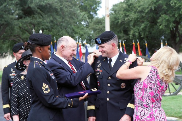 Maj. Gen. Perry Wiggins, deputy commanding general, U.S. Army North (Fifth Army), smiles as his father, Lamar, and wife, Annette, tackle pinning lieutenant general rank on him during his promotion ceremony, Sept. 4, 2013, at the historic Quadrangle on Fort Sam Houston, Texas. Immediately following the promotion, Wiggins assumed duties as commanding general, Army North, and senior commander for Fort Sam Houston and Camp Bullis.