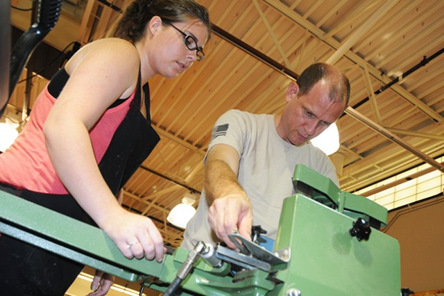 Brittany Aronson, recreational assistant, teaches Lt. Col. Mike Lightfoot, 23rd Flying Training Squadron, how to cut a corner for a photo frame at the arts and craft center Aug. 27.