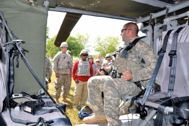 Sgt. Mark Toms, crew chief, with the 1-137th Aviation Battalion, 38th Combat Aviation Brigade, Indiana National Guard, gives a demonstration of how to properly lock the seatbelt during the aviation familiarization flight at Muscatatuck Urban Training Center, Ind. The Civilian Expeditionary Workforce receives an intense two-week training course prior to being deployed to conflict zones alongside the military.