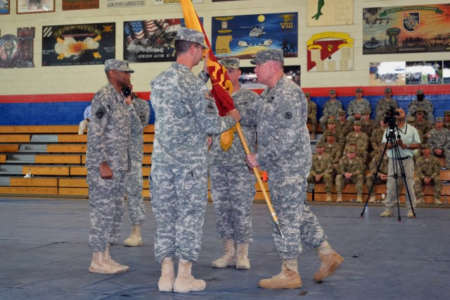 Maj. Gen. Thomas Richardson, commanding general, Military Surface Deployment and Distribution Command, passes the 595th Transportation Brigade command flag from Col. Andrew Peters to Col. David Banian during a change of command ceremony for the brigade at Camp Arifjan, Kuwait, Sept. 5, 2013.  As Banian assumes command of the SDDC brigade, Peters will move on to assume duties as executive officer to Army Materiel Command's deputy to the commander.