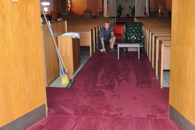 Fort Irwin's Center Chapel NCOIC Sgt. 1st Class Clifford Crum points out how water flooded the chapel's front door and seeped into the chapel carpet, up to the rear third and fourth row pews.