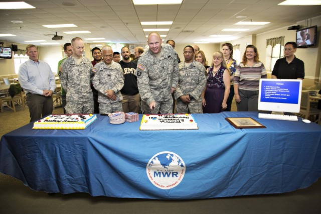 """PICATINNY ARSENAL, N.J. - Lt. Col. Jason Mackay, Picatinny Arsenal Garrison Commander (center) prepares to cut a birthday cake in celebration of the U.S. Army installation's 133rd birthday.  Picatinny's lineage is traceable to the year 1749 when local blacksmith Jonathan Osborne established the """"Middle Forge"""" at the foot of Picatinny Peak because the area was rich in iron ore and had an abundance of water. Picatinny Arsenal is the Joint Center of Excellence for Armaments and Munitions, providing products and services to all branches of the U.S. military."""