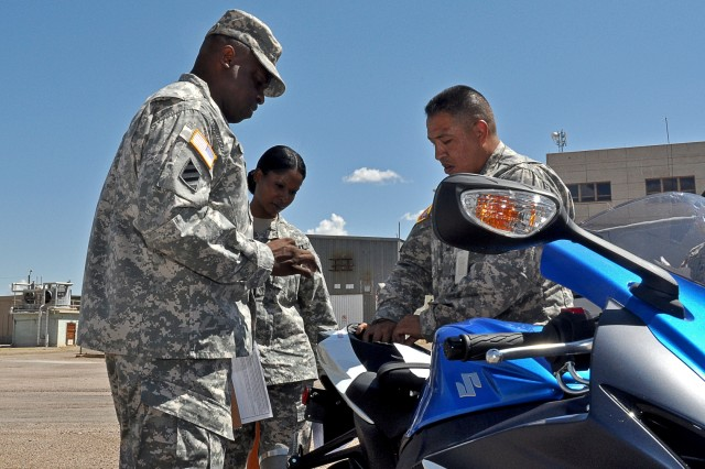 Master Sgt. Juan Muñoz (right) walks Sgt. Maj. St. Claire Allen (left) and Sgt. 1st Class Ladonna Thomas through the inspection of a sport bike.