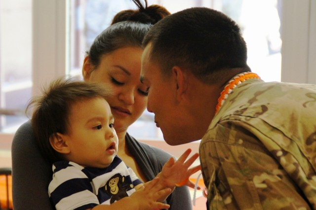 Spc. Alexander Harden, Co. A, 307th ESB, greets his wife, Darcel, and son, Isaiah, anxiously awaiting his return, August 6, at the battalion dining facility on Helemano Military Reservation, following the company's nine month deployment to Afghanistan.