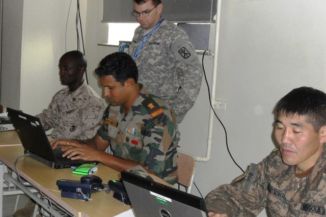 Chief Warrant Officer 2 Gregory MacDonald, 307th ESB Automations Technician, conducts Network, Share Portal instruction and a class on the use of the Request for Information tool to (seated, from left) Staff Sgt. Reginald Lamptey, 2nd Bn, 11th Marines, Camp Pendleton, Calif., Maj. Laxman Ganesh,  Indian Army, and Maj. Tsetsenkhuu Nanjid, of the Mongolian Armed Forces.
