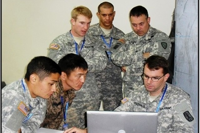 Chief Warrant Officer 2 Gregory MacDonald, 307th ESB Automations Technician (seated right), coaches exercise participants on adding a computer to a domain, verifying network services and using Share Portal.  His trainees include (from left) Pvt. 2nd Class Tadhg Nakada, 1st Battalion, 207th Aviation Regiment, Alaska Army National Guard; Staff Sgt. Munkhtulga Oyunbat, Mongolian Armed Forces and (standing) Sgt. Spencer Tilove and Sgt. Ramon Rodriguez Garcia, both with 307th ESB; and Sgt. First Class Darin Swain, also with the 1-207th.