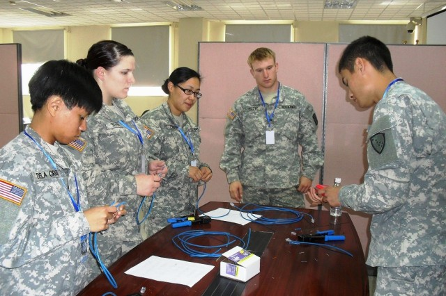 Sgt. Spencer Tilove, Co. B, 307th ESB (back) instructs (from left) Pfc. Beverly Dela Cruz, Pfc. Brittany Sissions, Sgt. Charline Peterson, and Pvt. 2nd Class Tadhg Nakada, all with the 1st Battalion, 207th Aviation Regiment, Alaska Army National Guard S-6 team, how to install RJ45 connectors on Category 5 cables.
