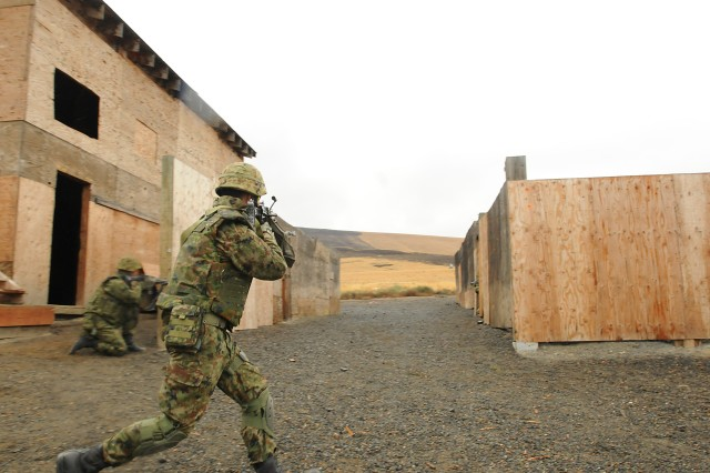 Members of the 16th Regimental Combat Team, Japanese Ground Self Defense Force, traverse open areas and clear buildings in the urban operation complex at Yakima Training Center, Wash., Sep 6. The Soldiers are taking part in Operation Rising Thunder 13 alongside members of the 5th Battalion, 20th Infantry Regiment. It was a learning event for both forces, as the units took turns observing each other traverse the course. The three-week combined training event is designed to exercise and develop all war-fighting functions for both Japanese and U.S. forces.