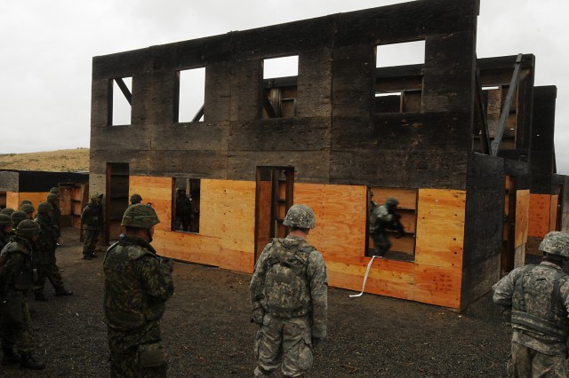 Soldiers assigned to B Company, 5th Battalion, 20th Infantry Regiment, clear a room while maneuvering through the urban assault complex at Yakima Training Center, Wash., Sep. 6. The Soldiers are taking part in Operation Rising Thunder 13 alongside members of the 16th Regimental Combat Team, Japanese Ground Self Defense Force. It was a learning event for both forces, as the units took turns observing each other traverse the course.  The three-week combined training event is designed to exercise and develop all war-fighting functions for both Japanese and U.S. forces.