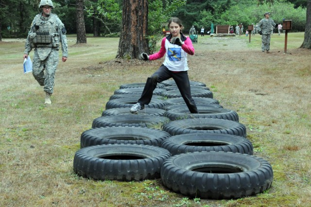 A spouse of a soldier assigned to the 1st Squadron, 14th Cavalry Regiment jumps from tire-to-tire during the grenade lane portion of 1-14 Cav's Spouse Spur Ride held at Joint Base Lewis-McChord, WA., Sept. 5. The spouses conducted tire runs, low crawled under barbed wire and sprinted from station-to-station until all half-dozen stations were complete and the mockups were neutralized at this event.  (U.S. Army photo by Staff Sgt. Chris McCullough)