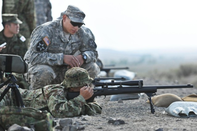 Pfc. Chris Alicea, sniper, 5th Battalion, 20th Infantry Regiment, 3rd Stryker Brigade Combat Team, 2nd Infantry Division, watches as Sgt. Yuusuke Nakasato, 16th Regimental Combat Team, 4th Division, Japan Ground Self-Defense Force, aligns his sights to a target during a live-fire training exercise in which American and Japanese snipers exchanged knowledge of their sniper operation procedures, Sept. 5, 2013, at the Yakima Training Center, Wash. The combined training is part of Operation Rising Thunder 13, a three-week training exercise between soldiers from I Corps and the 16th RCT, designed to develop all war-fighting functions for both Japanese and U.S. forces.