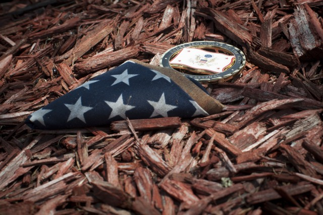 Pictured is one of the coins left by Under Secretary of the Army Dr. Joseph W. Westphal as he paid his respects at Warriors Walk, which honors the fallen Soldiers of the 3rd Infantry Division and attached units, who served in Operation Iraqi Freedom, Operation New Dawn, and Operation Enduring Freedom at Fort Stewart, Ga., Sept. 5, 2013. Soldiers are memorialized with an Eastern Redbud tree planted in their honor. The purpose of Westphal's visit was to underscore the versatility of the force to posture for future requirements and as well as to highlight the concerns of senior Army leaders about the impact of fiscal constraints (furloughs) and reinforce the value/contributions of the Department of the Army Civilian workforce and their families.