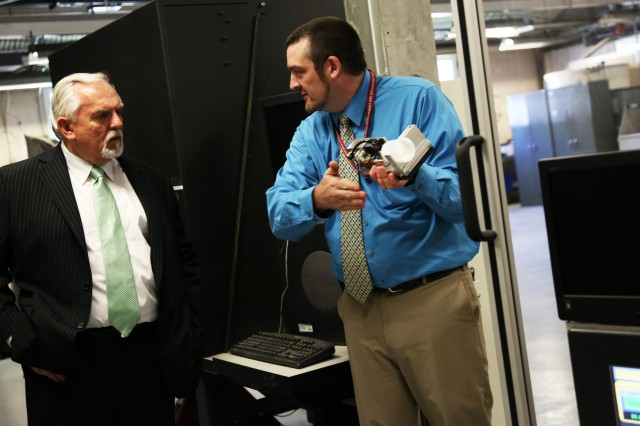 During a tour of Picatinny Sept. 4, James Zunino (right), Picatinny Materials Engineer, shows actor John Ratzenberger a modular tool that can be added onto the Multi-Axis Modular Manufacturing Platform for additive manufacturing. Different tools allow the machine to perform different manufacturing techniques.