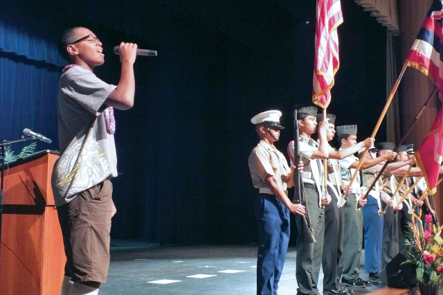 Zion Fetui (left) of Pearl City Highlands Intermediate School performs the National Anthem as cadets with the Junior Reserve Officer Training Corps Joint Color Guard display an array of flags to open the 12th annual Joint Venture Education Forum at The Salvation Army-Ray and Joan Kroc Corps Community Center, here, Aug. 29.