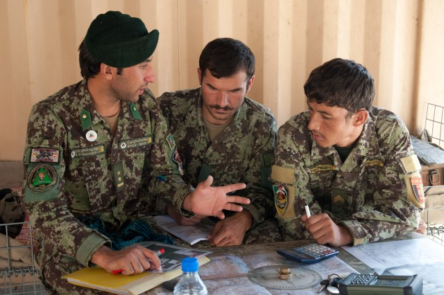 "KAPISA PROVINCE, Afghanistan "" Afghan National Army Lt. Yosuf (left), a fire support officer from 4th Kandak, 3rd Brigade, 201st Corps, discusses plotting targets with his soldiers at Forward Operating Base Tagab, Kapisa Province, Afghanistan, Sept. 3, 2013. U.S. Army Soldiers from Battery B, 5th Battalion, 25th Field Artillery Regiment, 4th Brigade Combat Team, 10th Mountain Division, traveled from FOB Gamberi in Laghman Province to advise and instruct ANA artillery soldiers throughout eastern Afghanistan on the proper handling of D-30s, a Soviet-made heavy artillery weapon capable of engaging targets more than 15 kilometers away. This particular visit by Battery B served to check on training and certify the ANA D-30 howitzer crews. (U.S. Army National Guard photo by Sgt. Margaret Taylor, 129th Mobile Public Affairs Detachment/RELEASED)"