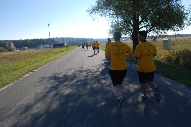Two Soldiers running in the 3-kilometer Suicide Prevention Awareness Run/Walk Sept. 6 at U.S. Army Garrison Ansbach's Urlas Housing pass through a brief shadow along the route.