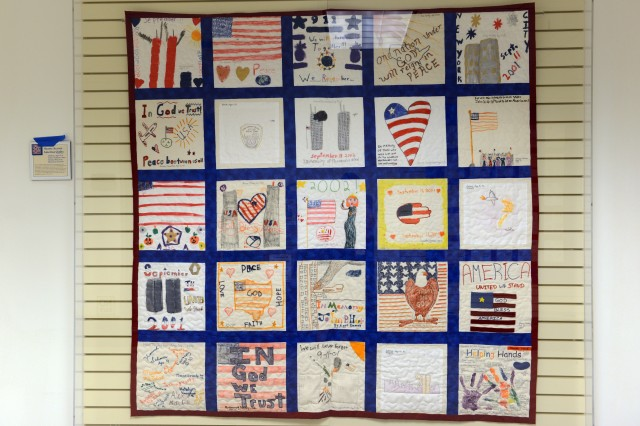 A Hearts Across America Quilt hangs in the Pentagon hallway. The quilt was made by children in six states and contains patriotic themes and themes of heartbreak and loss.