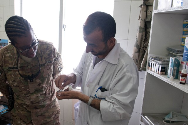 Capt. Akeele Johnson, a dentist with 4th Brigade Combat Team, 10th Mountain Division, watches while Senior Capt. Abdul Hadi, an Afghan Border Police dentist, demonstrates a dental technique Aug. 29 during an advisory visit to the clinic at ABP Zone 1 headquarters, Jalalabad, Nangarhar province, Afghanistan. The clinic sees to the medical and dental needs of Afghan police officers in Zone 1, comprised of eastern Afghanistan's Nangarhar, Nuristan and Kunar provinces.